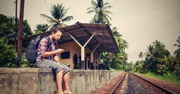 Junger Mann mit Handy auf Reisen