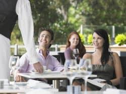 Junges Paar unterhält sich mit dem Kellner