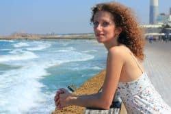 Junge Frau blickt auf das Meer