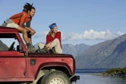 Zwei junge Leute sitzen auf einem Jeep