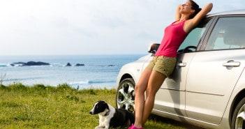 Junge Frau mit Hund an Auto gelehnt